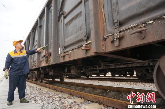 沿着列车车厢走,货检员每天都能走出一个马拉松的距离。 韩章云 摄