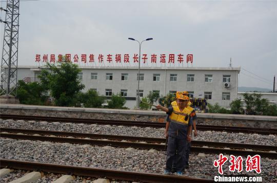 """长子南站的货检员们穿过铁路为列车找""""病因""""。 韩章云 摄"""