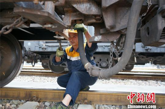 """一把小锤敲敲打打,货检员就能为万吨重载列车找出""""病因""""。 韩章云 摄"""