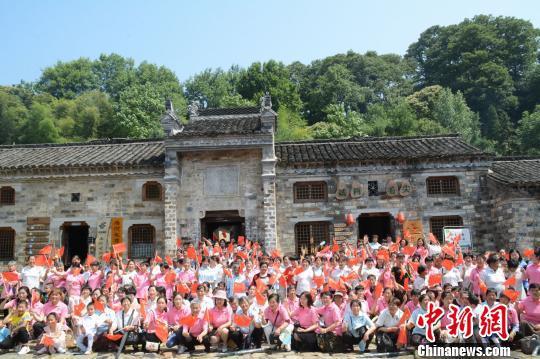 端午佳节,400多名西河湾的外嫁女集体回乡探亲。图为外嫁女在西河古民居前合影。 张因祥 摄