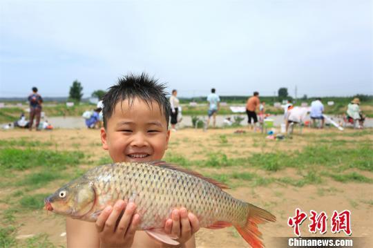 成功摸到大鲤鱼让小朋友开心不已 徐志清 摄