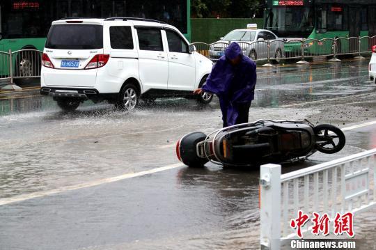 郑州市区,骑行者扶起滑倒的电动车。 王中举 摄