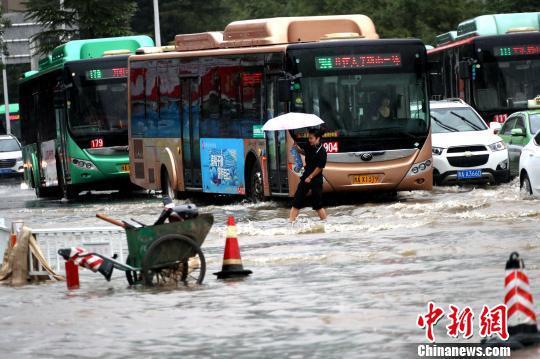 郑州市区,公交车在积水中行驶。 王中举 摄