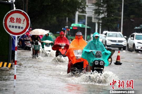 """郑州市区,电动车""""破浪""""前行。 王中举 摄"""