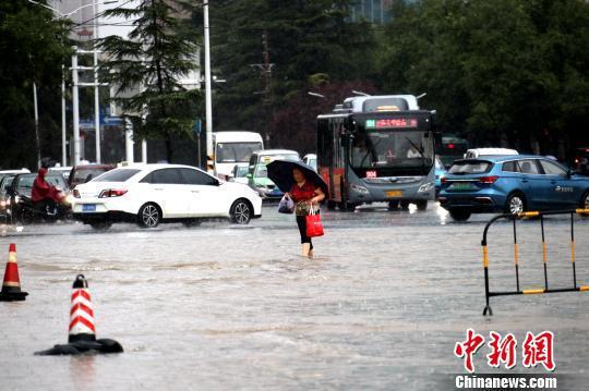 郑州市区,市民行走在没入脚踝的水中。 王中举 摄