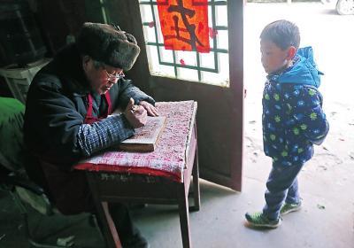 小男孩好奇地背着双手认真观看张连生老先生雕刻木版画