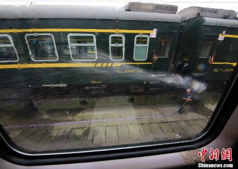 洗车工用水冲洗列车外部。