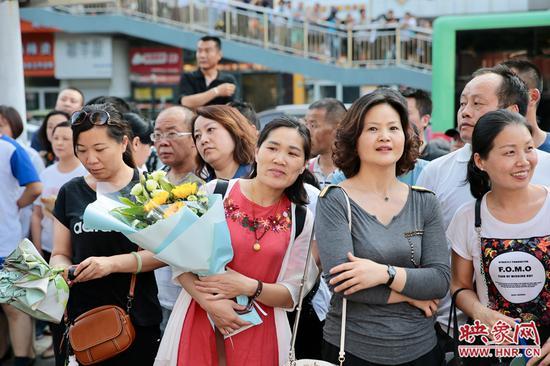 家长们双手抱着鲜花,等待考试结束。