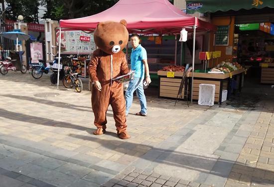 图为赵素彬扮演的玩偶熊在街头派发传单