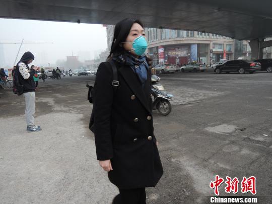 一位路人戴着防雾霾口罩匆匆而过。 韩章云 摄