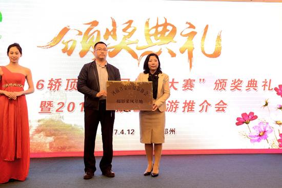 """河南省旅游摄影协会秘书长杨志威向轿顶山景区授予""""摄影采风基地""""称号"""