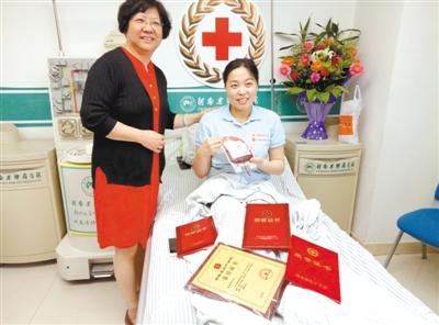 张晓丽手拿她捐献的造血干细胞很开心,与上海接受方代表吴颖菊合影