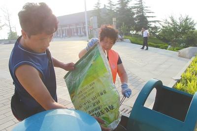 李新安帮母亲把垃圾倒入垃圾箱