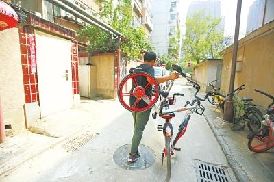 有些共享单车由于太阳能板被杂物遮挡,单车运营专员无法开锁,只能摞起来推着走。
