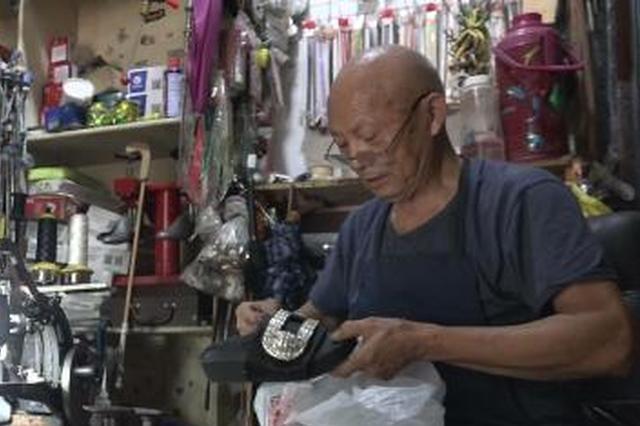 图为顾客在时美龙的店里,一边等待修鞋,一边和老人聊天。 阚力 摄