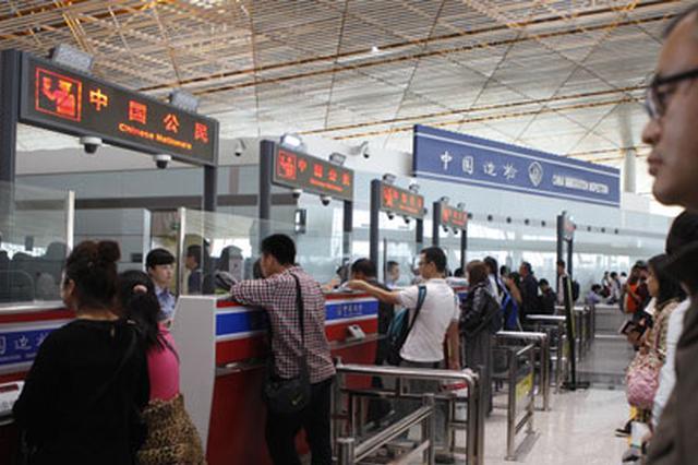 资料图:出境游的中国公民在首都机场入境处签入境章。中新社发 杨可佳 摄