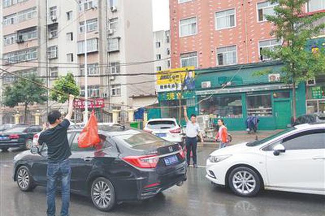 """郑州街头线缆垂落 几男子雨中化身""""托举哥"""""""