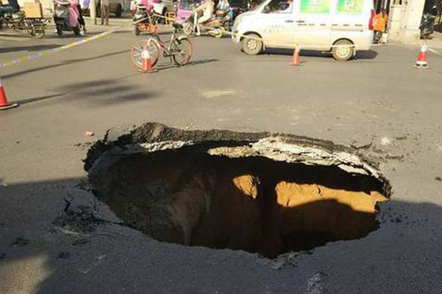 郑州一路口突现直径3米大坑 过路公交车后轮卡其中