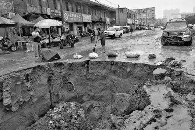 郑州一路段出现塌坑 志愿者暴雨中引导市民绕行