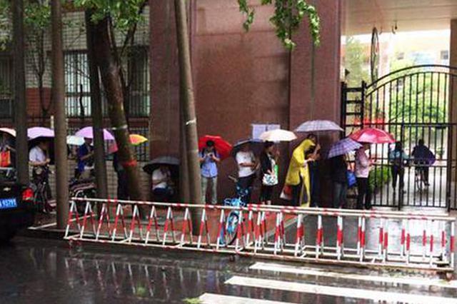 郑州小学新生报名首日 学校门口家长雨中排队