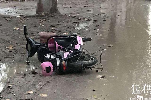 郑州女子雨中骑电动车出现故障 一怒之下弃车走人