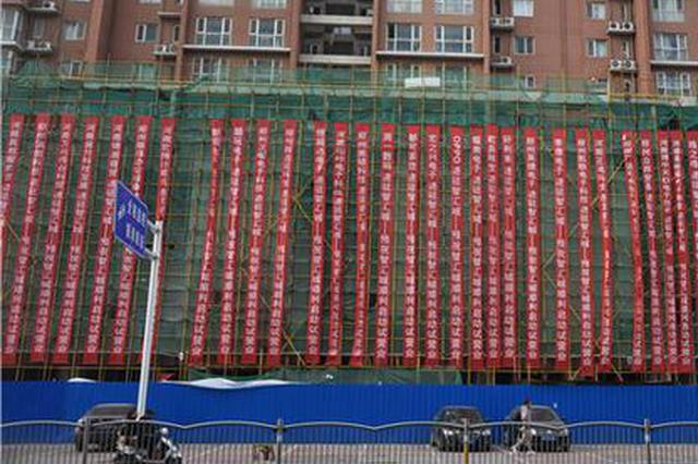 郑州一商住楼外墙挂满条幅 市民:太扎眼