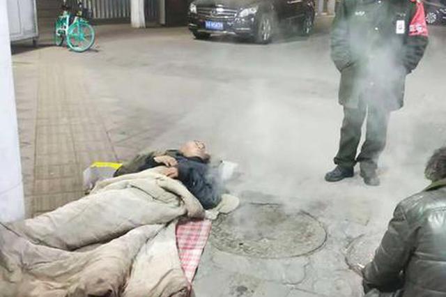 郑州两名流浪者蜷在热力井盖上取暖 被劝进救助站