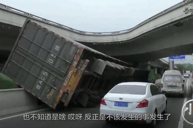 郑州大货车急打方向后翻车钻入桥下 只因没留神限高