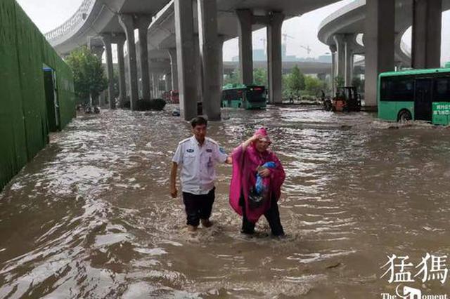 """郑州大雨袭城 巡防队员站在街头水里给行人""""导航"""""""