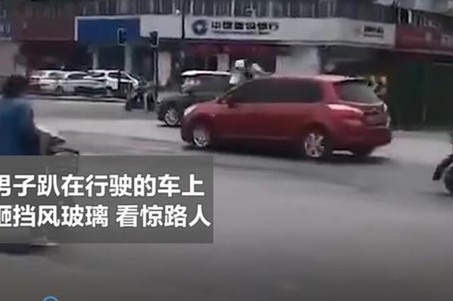 开封男子趴在行驶的车上怒砸挡风玻璃 看惊路人