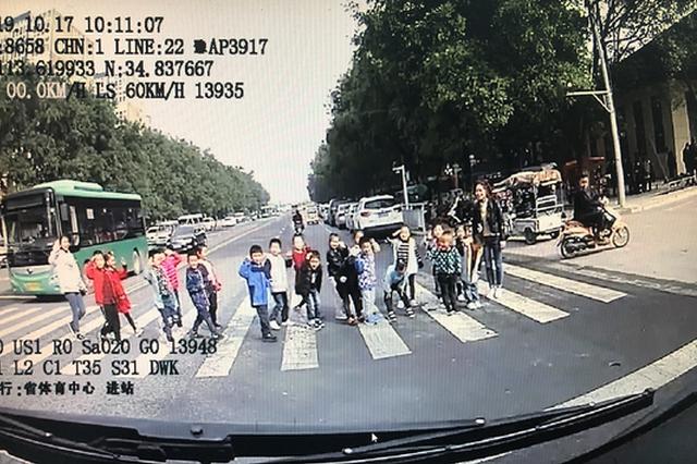 郑州公交停车让行 斑马线上一群孩子齐刷刷鞠躬