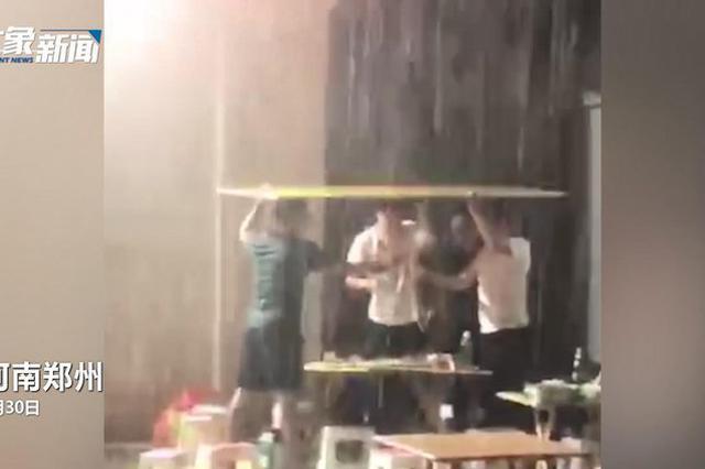 奇葩!郑州4男子聚餐遇大雨 顶着广告牌继续吃