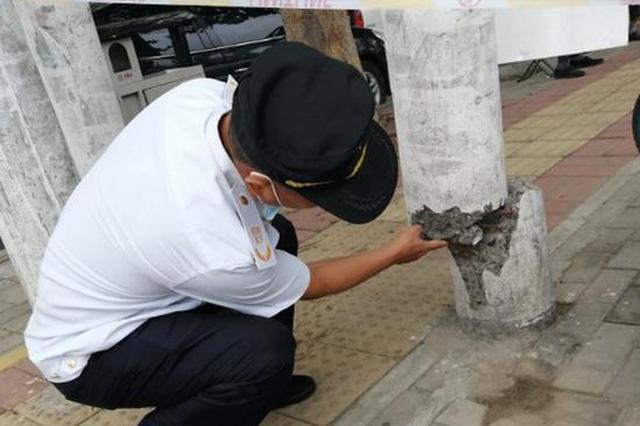 郑州一电线杆根部断裂悬空 巡防队员紧急提醒