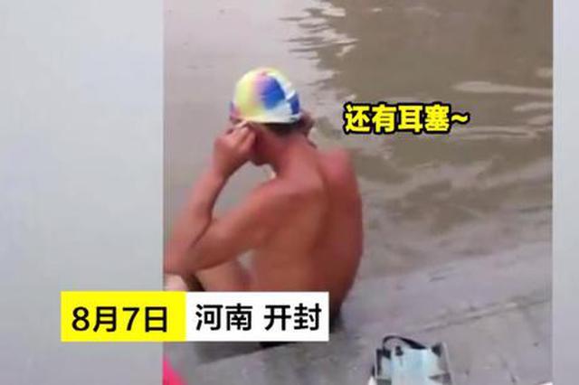 开封暴雨后马路变泳池 男子一身泳装跳进水中撒欢