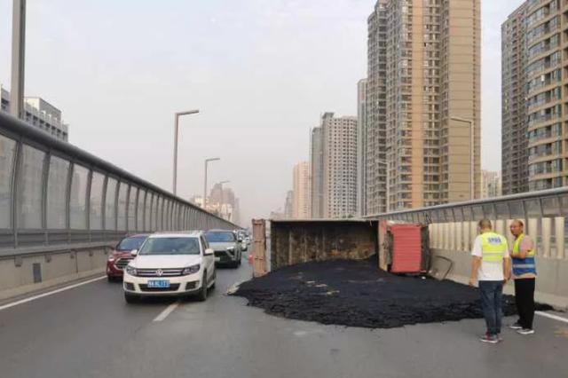 郑州一货车侧翻高架 致交通管制!撒了一地黑色沥青