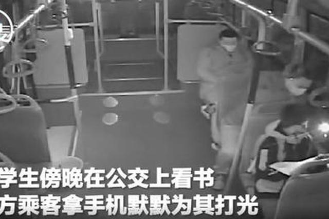 郑州一小学生公交上看书 后方乘客默默为其照明