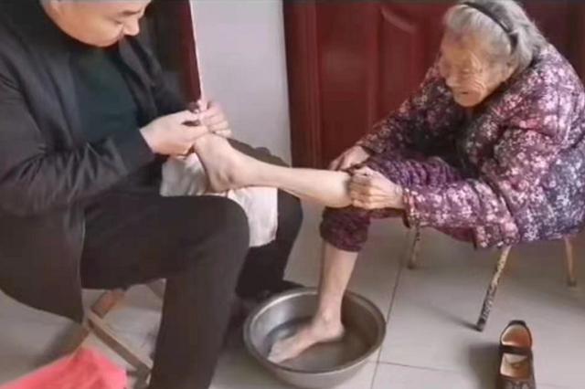 儿子怀抱91岁母亲的脚精心打理,网友:大赞之后是惭愧