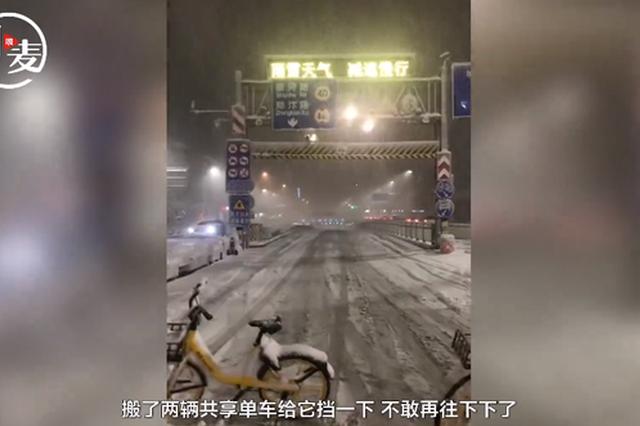 郑州突降大雪隧道被堵死 父子俩搬来共享单车提醒路人绕行