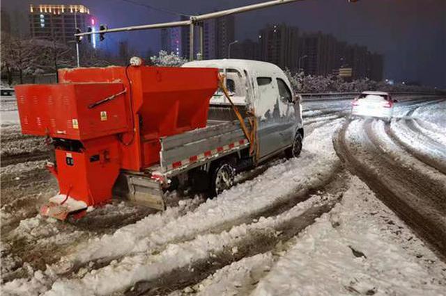 登封大雪为避免路面结冰 环保人连夜为市民打造出行之路