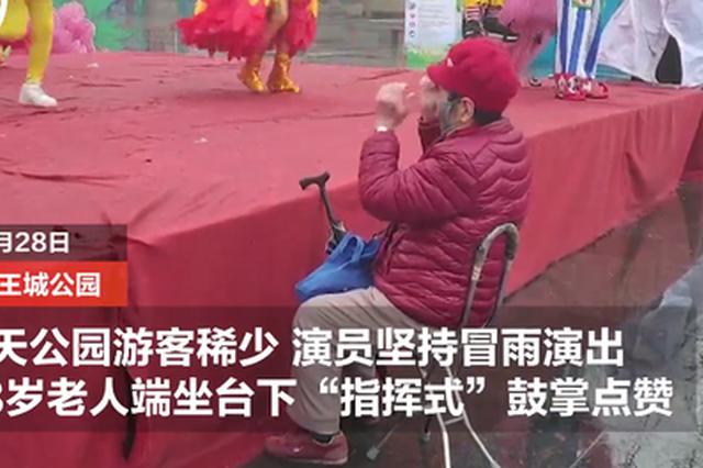 洛阳雨天演员坚持冒雨演出 88岁老人台下端坐鼓掌点赞