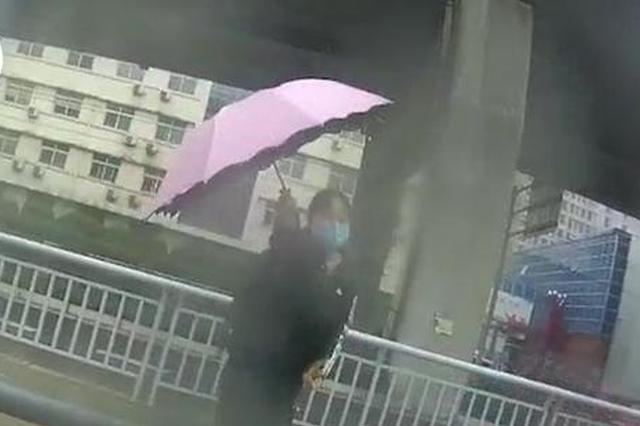 辅警路上执勤被雨淋透 热心市民递出自己的雨伞为其遮挡