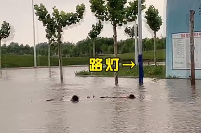 危险!周口俩熊孩子竟在道路积水路段泡澡