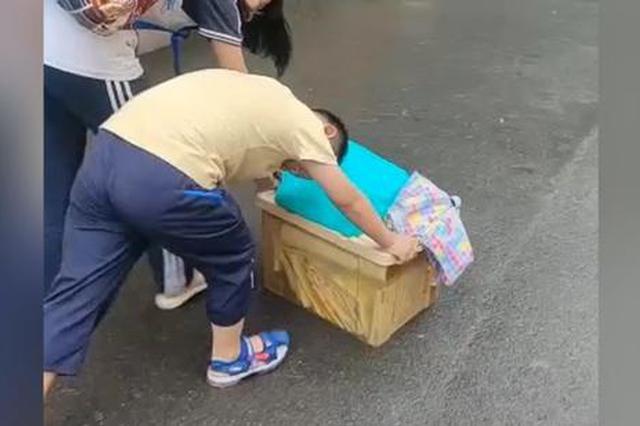姐姐放假行李太重 弟弟搬不动弯着腰一路帮姐姐推着行李箱走