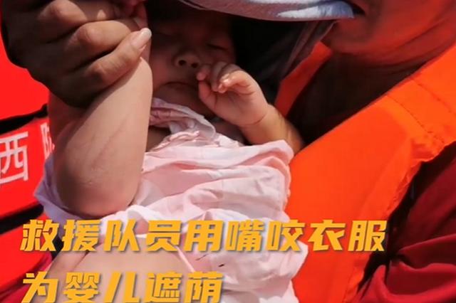 河南新乡:救援队员用嘴咬衣服为婴儿遮荫