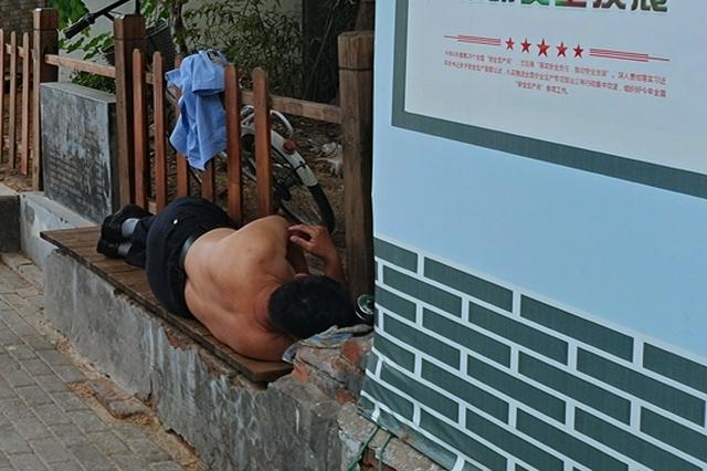 忙抗疫工作熬夜劳累 郑州一保安躺路边就睡着