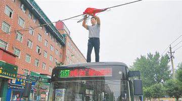 闹市街头线缆垂落 男子雨中化身托举哥