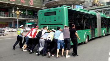 郑州公交车坏在路中间 众人合力推车