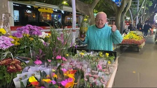 郑州聋哑老人夜晚三轮车摆满鲜花 穿蓝色毛衣微笑拍照充满幸福