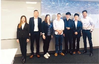 今年9月,庄凌(右三)与学校团队成员在英国卡迪夫向合作公司展示营销项目方案。