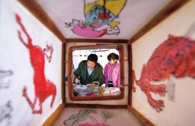 木版灯笼画传承人张四清在做灯笼画时,孙女在一旁观看。